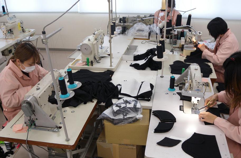 縫製工場でミシンを使って仕事しているグループ